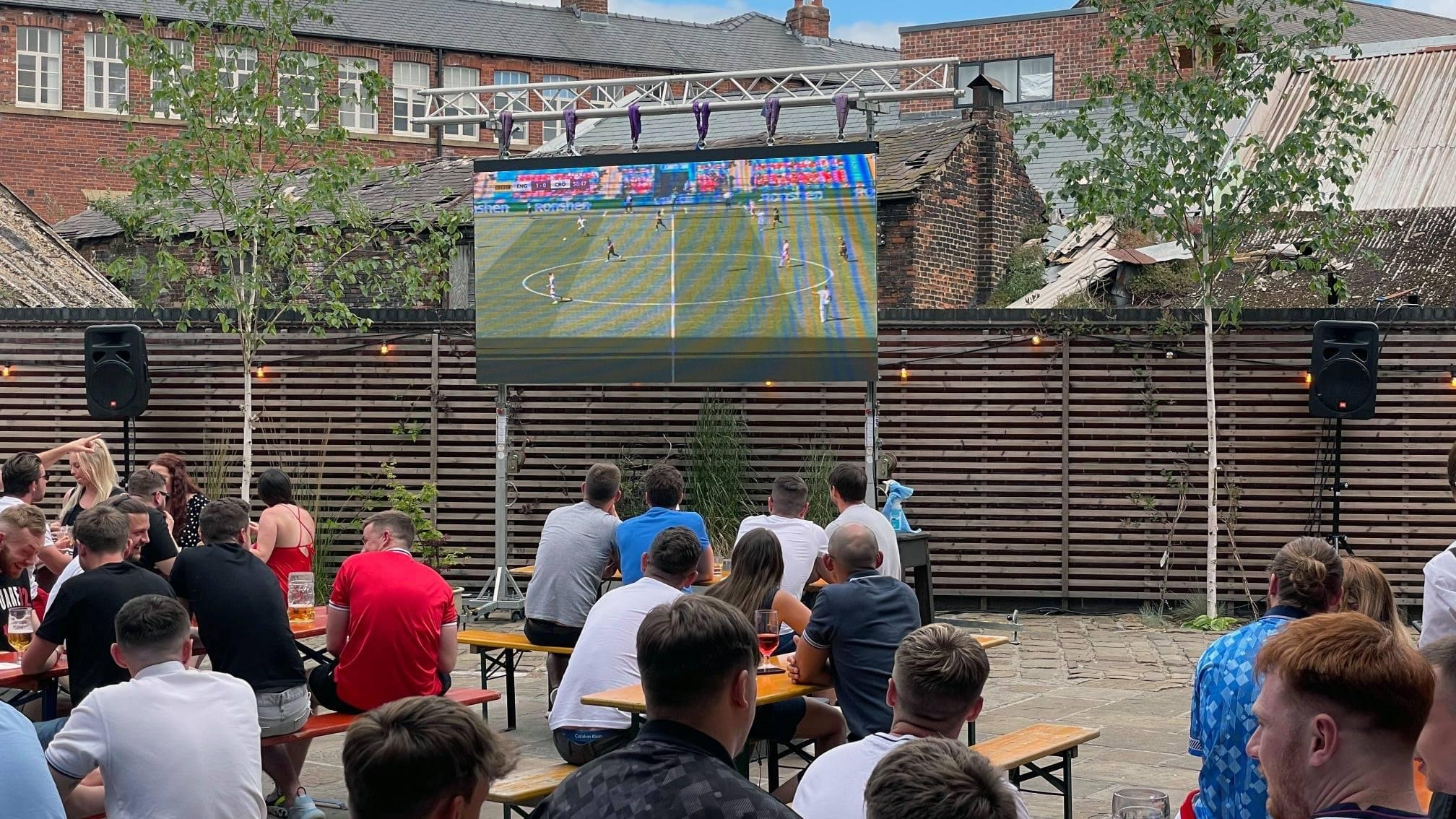 LED Screen in venue courtyard showing football